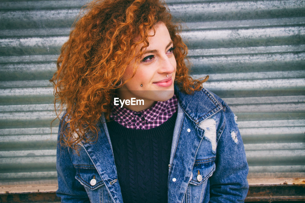 Close-Up Of Young Hipster Woman Against Metal Shutter