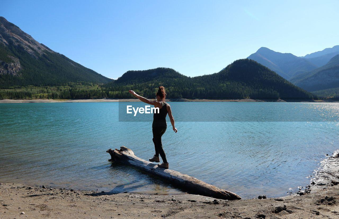 Woman walking on log in lake against clear sky