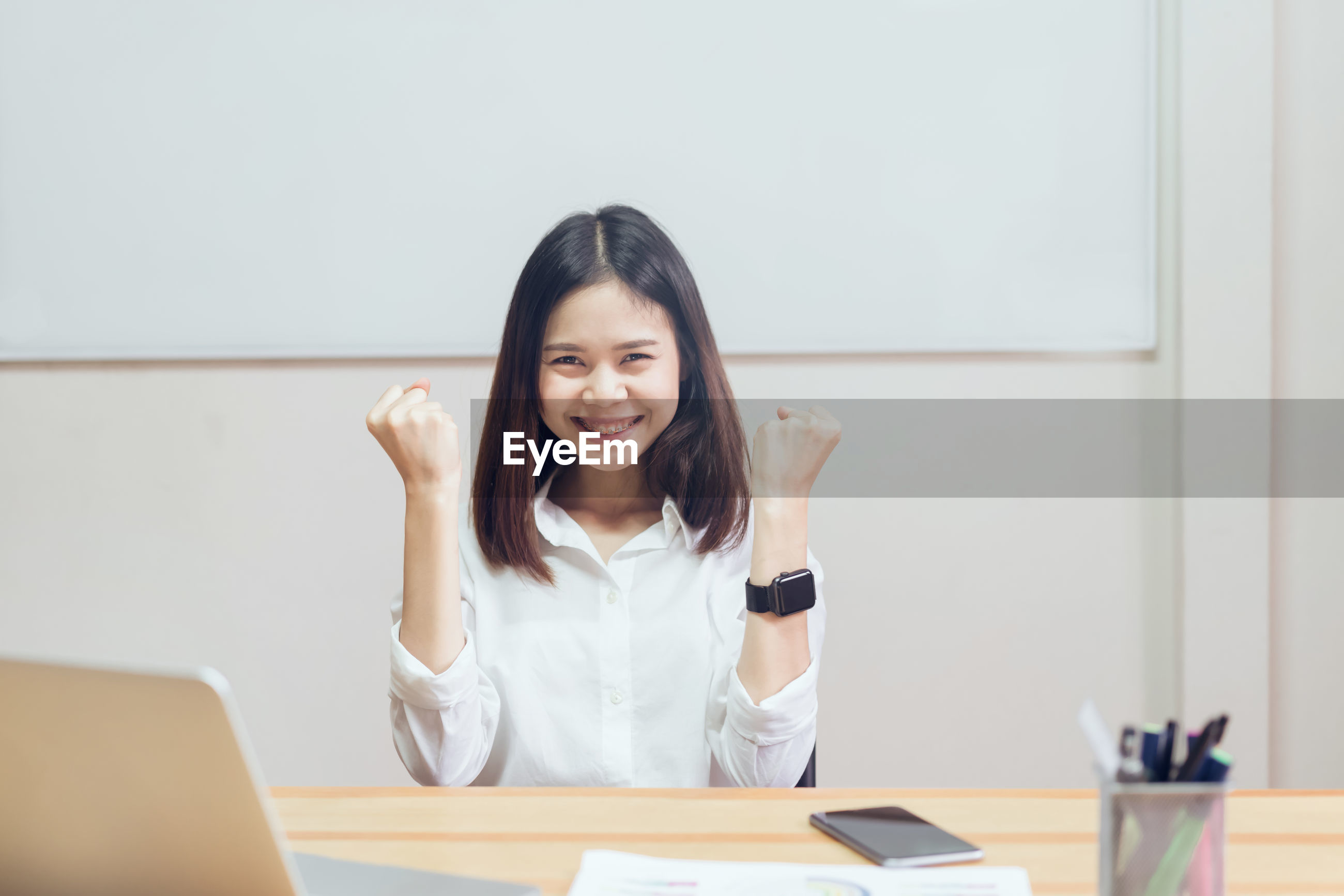 Portrait of happy businesswoman gesturing while sitting on desk at office