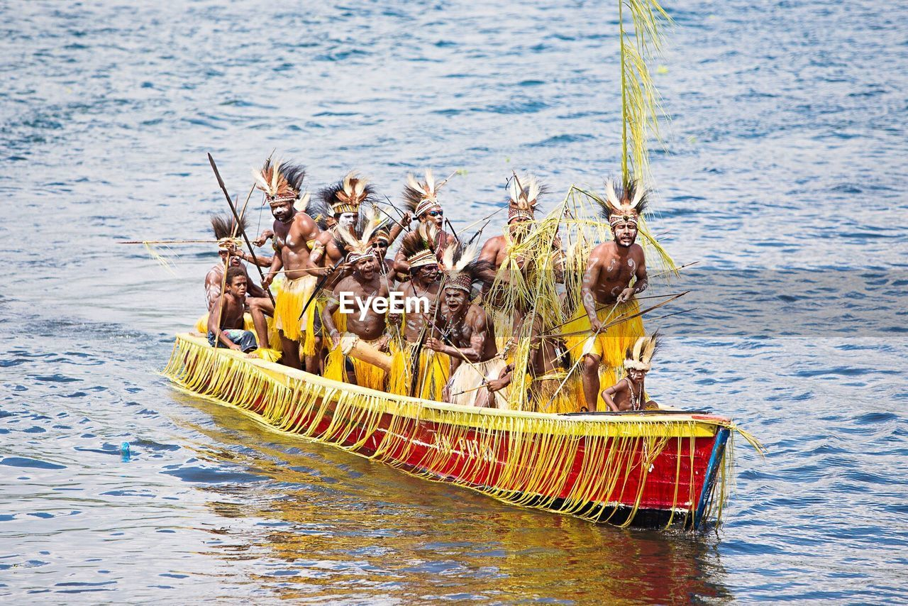Group of people in traditional outfit on canoe