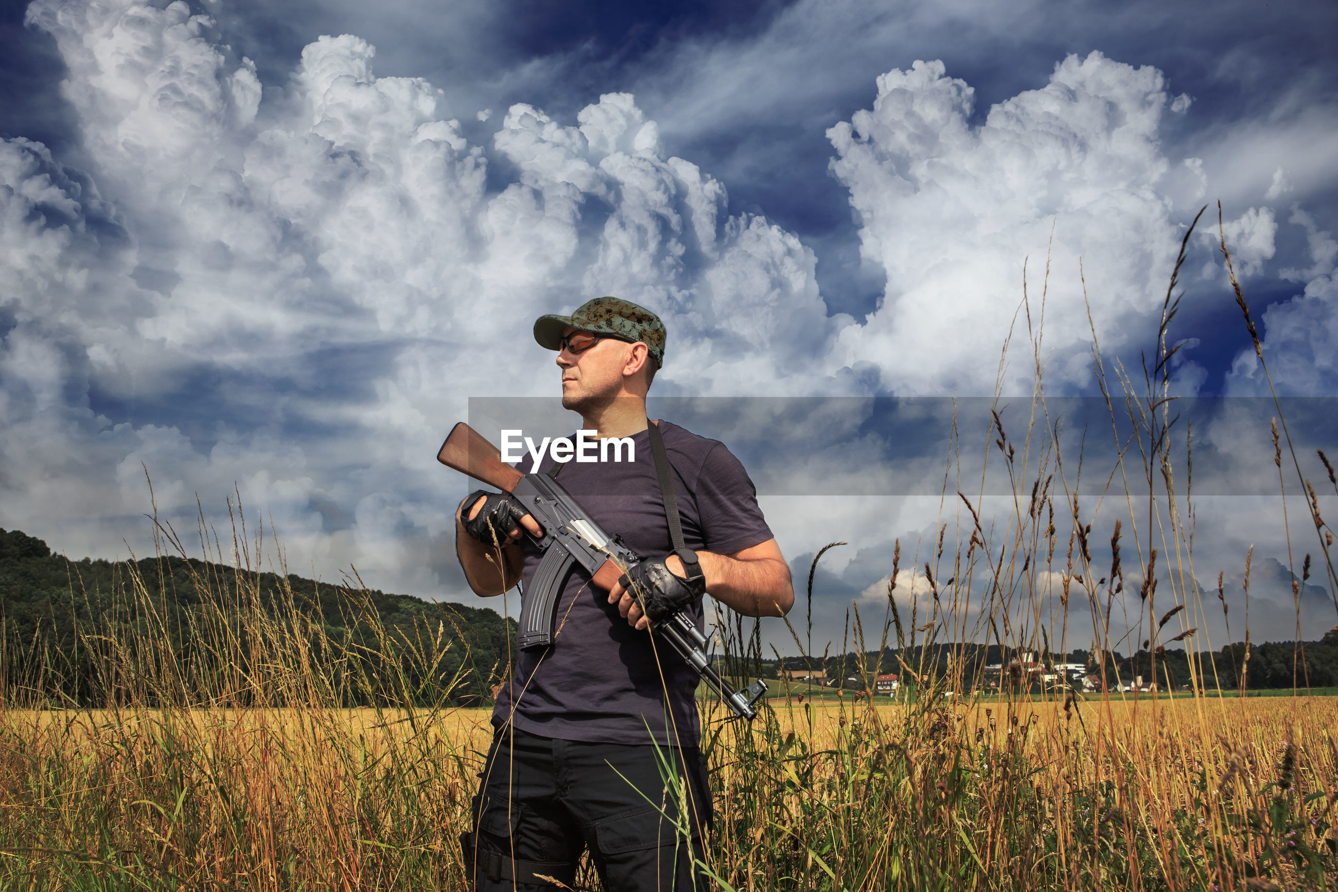 Man holding rifle standing against sky
