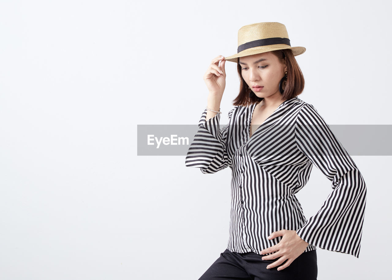 studio shot, striped, hat, one person, clothing, copy space, young adult, indoors, white background, young women, three quarter length, standing, cut out, front view, lifestyles, casual clothing, beauty, women, beautiful woman, hand, hairstyle