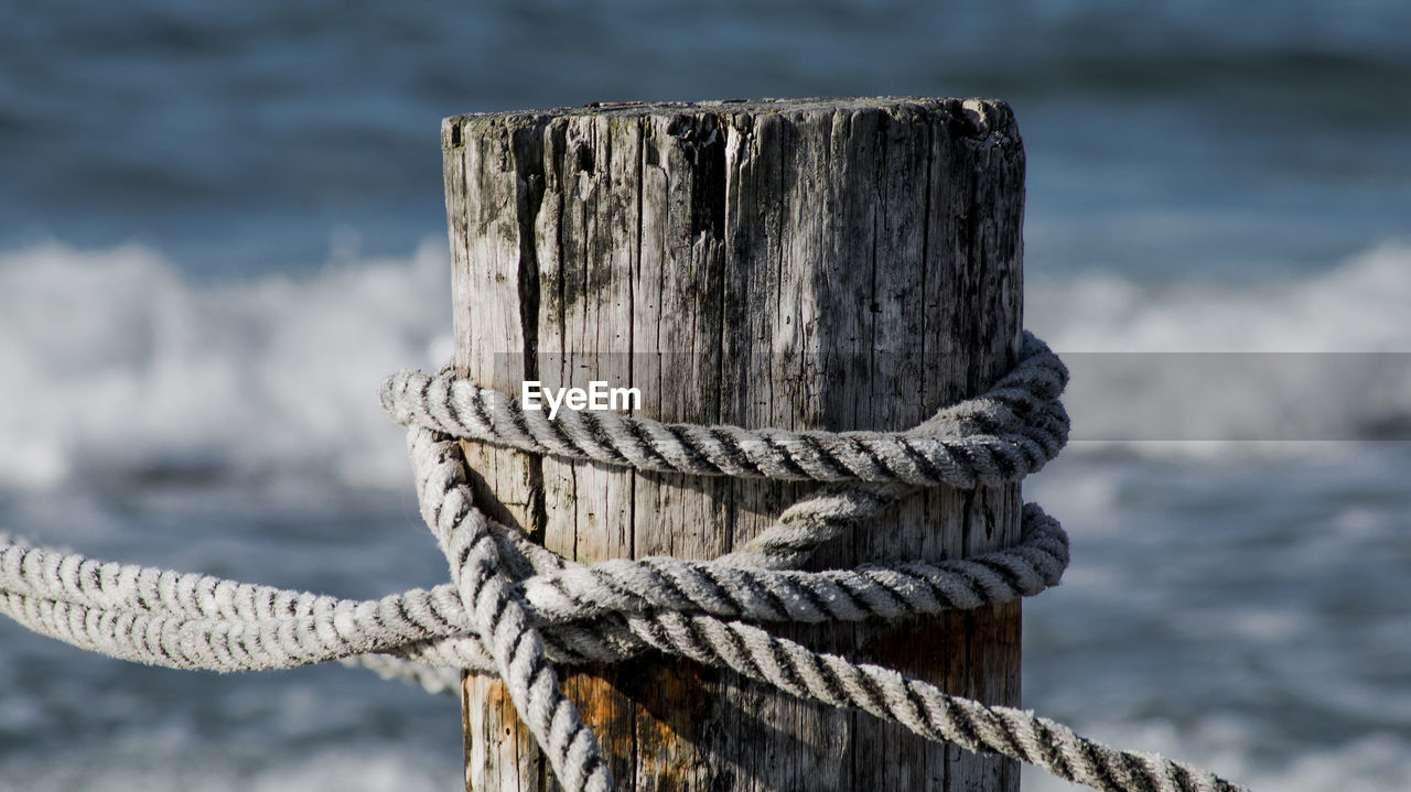 Close-up of wooden post with rope at beach