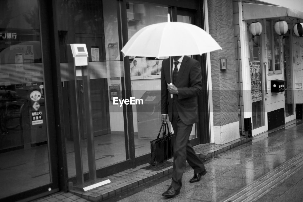 FULL LENGTH OF MAN WITH UMBRELLA WALKING IN BUILDING