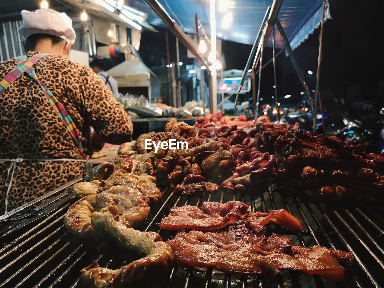 food, food and drink, freshness, meat, real people, preparation, market, night, one person, for sale, barbecue, business, retail, choice, incidental people, smoke - physical structure, variation, abundance, grilled, preparing food, street food, retail display