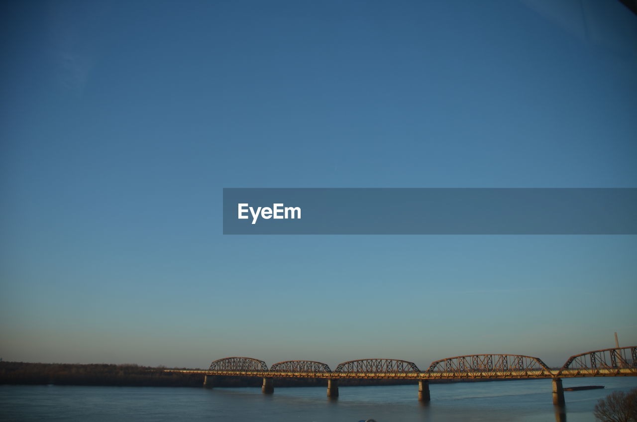 bridge - man made structure, copy space, clear sky, connection, architecture, built structure, outdoors, blue, day, water, transportation, river, sky, no people, bridge, nature