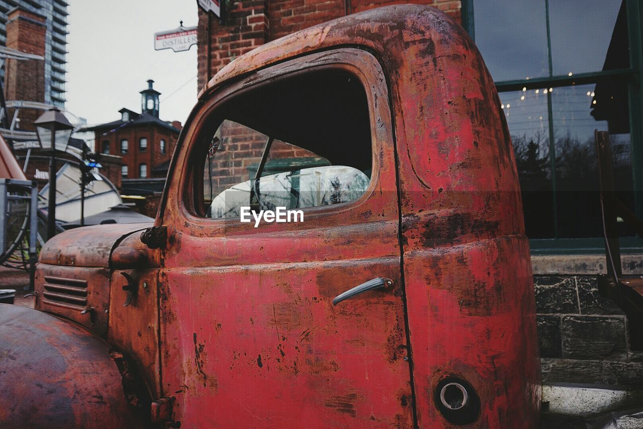 damaged, abandoned, transportation, rusty, obsolete, mode of transport, deterioration, weathered, land vehicle, run-down, car, day, no people, bad condition, outdoors, red, architecture, fire engine, close-up