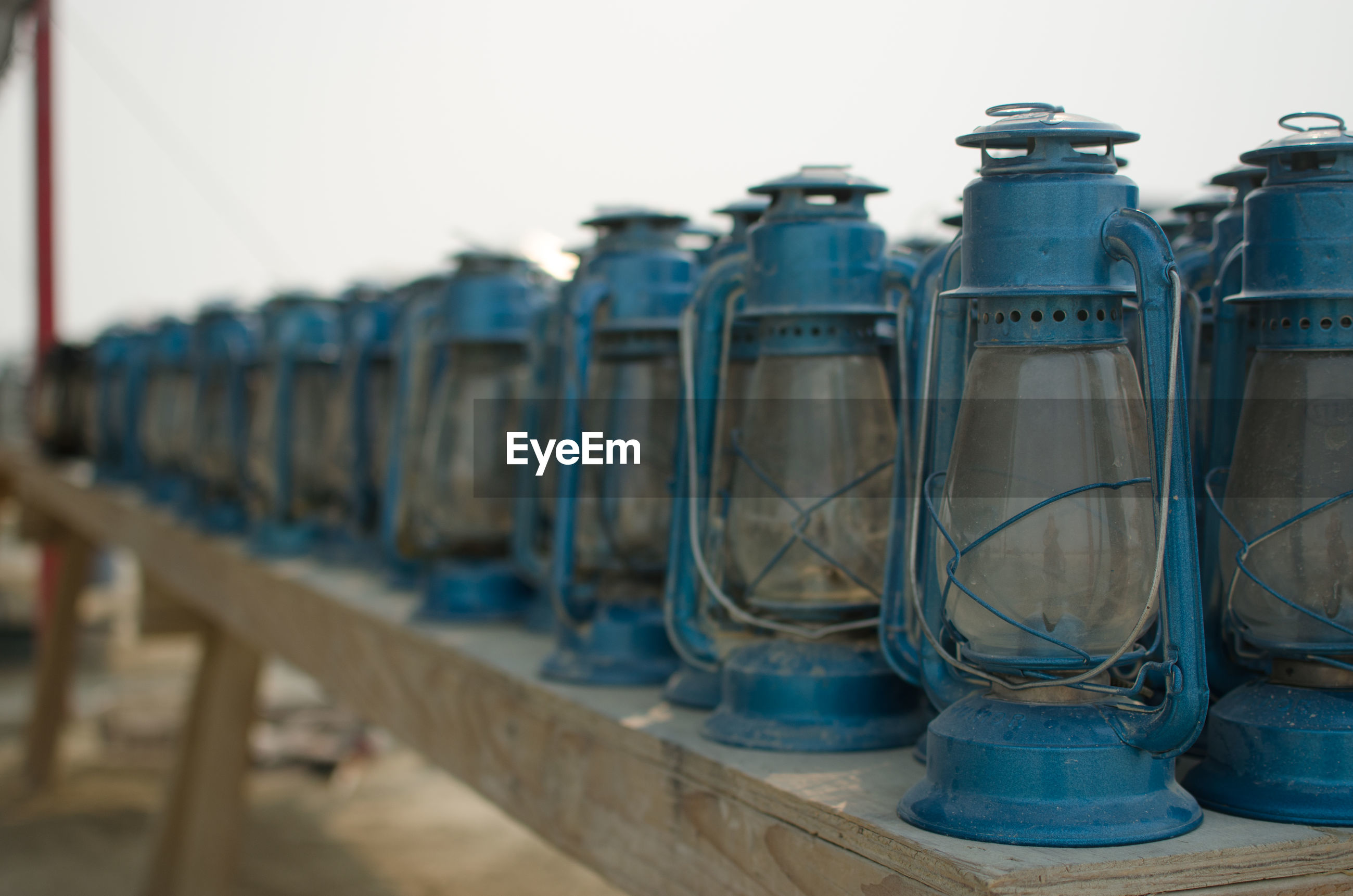 Close-up of blue lanterns on table against sky