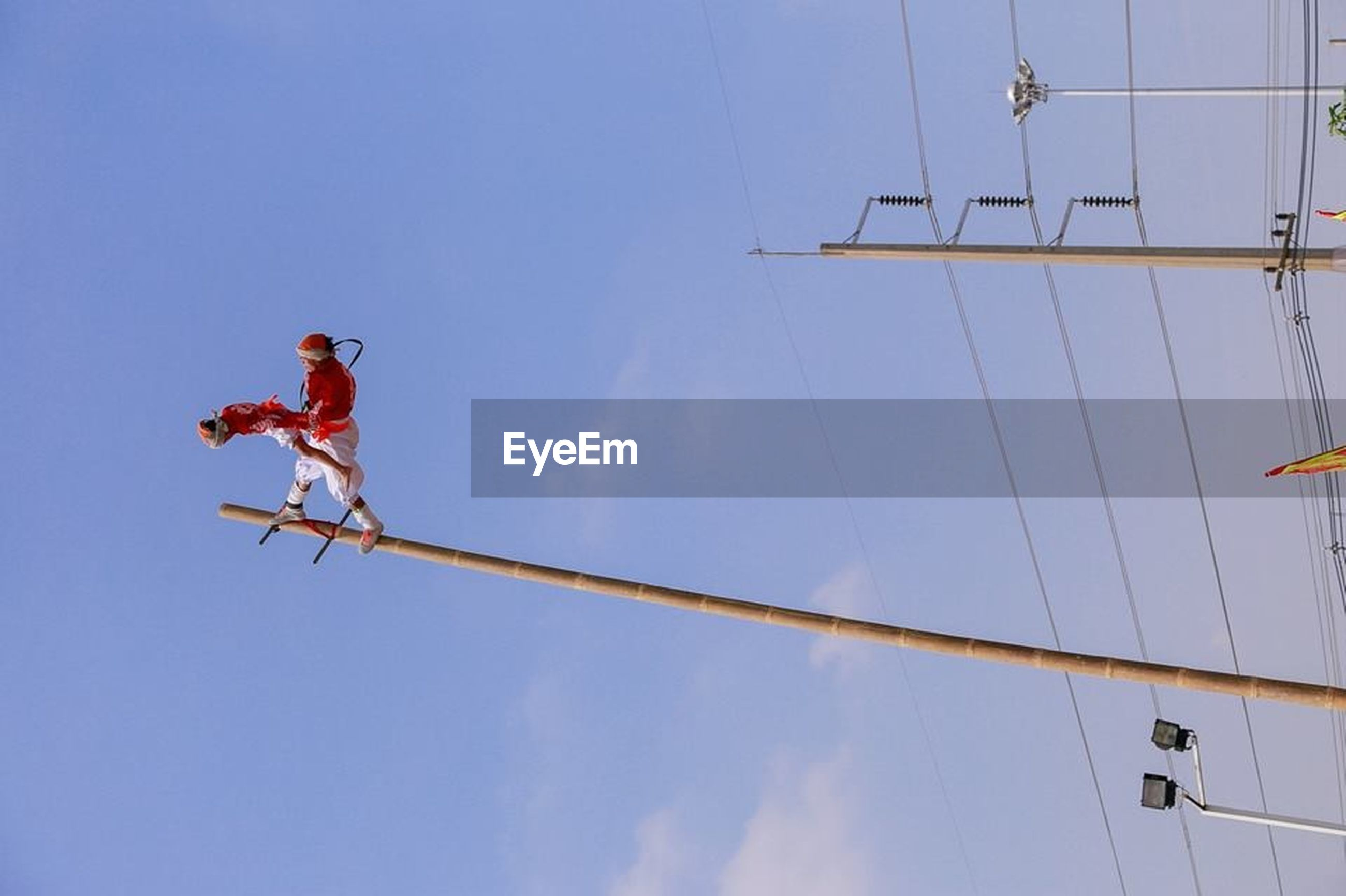 low angle view, clear sky, blue, sky, flying, mid-air, hanging, teamwork, day, air vehicle, outdoors, copy space, freedom, motion, technology, rope, men, full length, extreme sports, cable