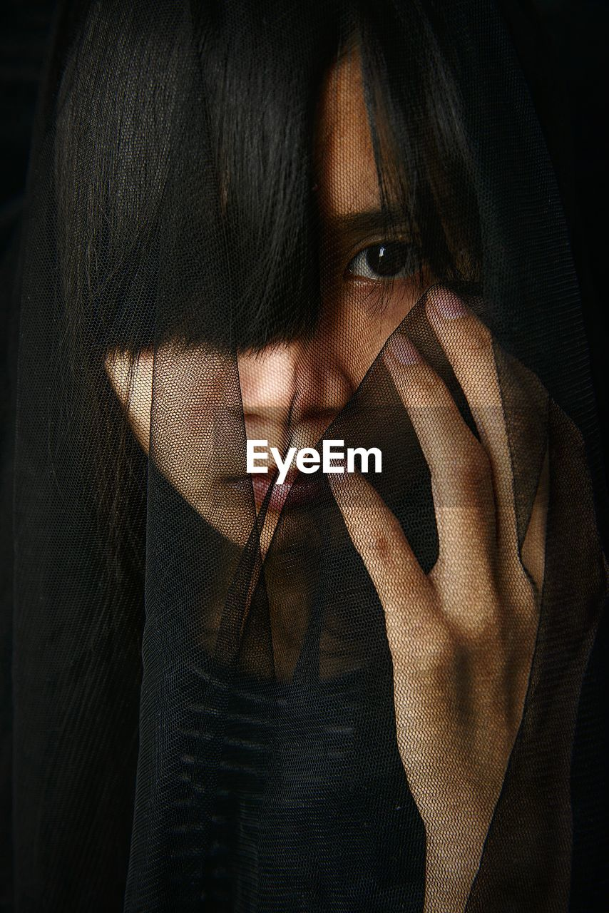 one person, portrait, women, real people, young adult, young women, front view, headshot, lifestyles, emotion, adult, indoors, looking at camera, leisure activity, veil, close-up, sadness, looking, contemplation, beautiful woman, hairstyle, depression - sadness, dark, black background, human face, bangs