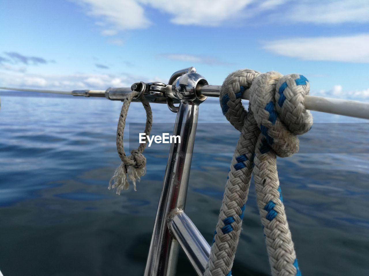 water, rope, tied up, strength, nautical vessel, sea, close-up, connection, transportation, metal, tied knot, mode of transportation, no people, nature, day, focus on foreground, sky, safety, outdoors, steel, alloy, nautical equipment