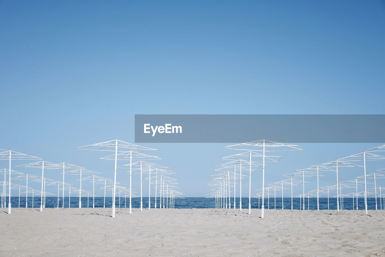 sky, copy space, blue, land, clear sky, beach, nature, day, sand, no people, outdoors, in a row, sea, architecture, tranquility, built structure, fuel and power generation, beauty in nature, environment, water