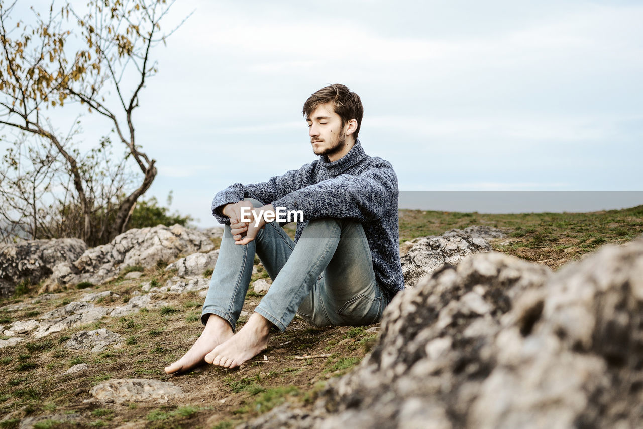 Portrait of young man sitting on rock