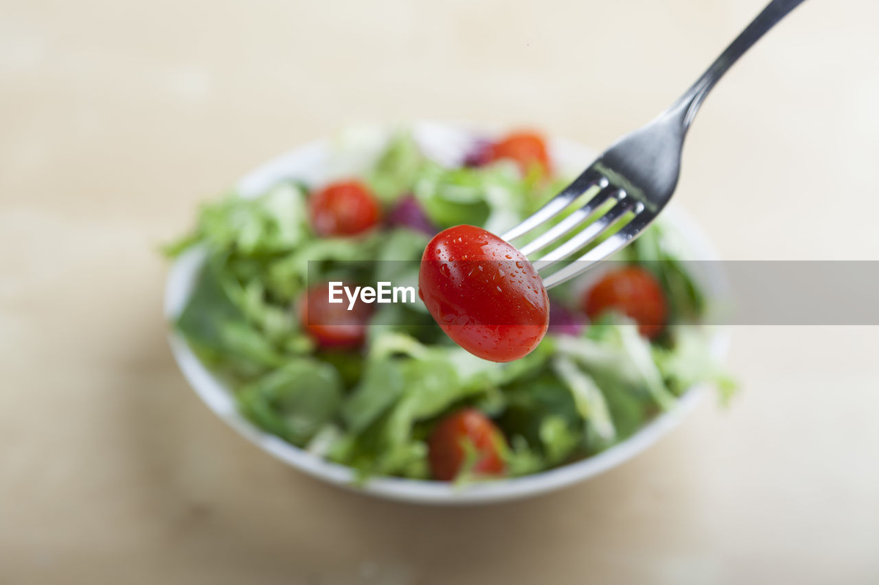 Fork Holding Cherry Tomato Over Salad