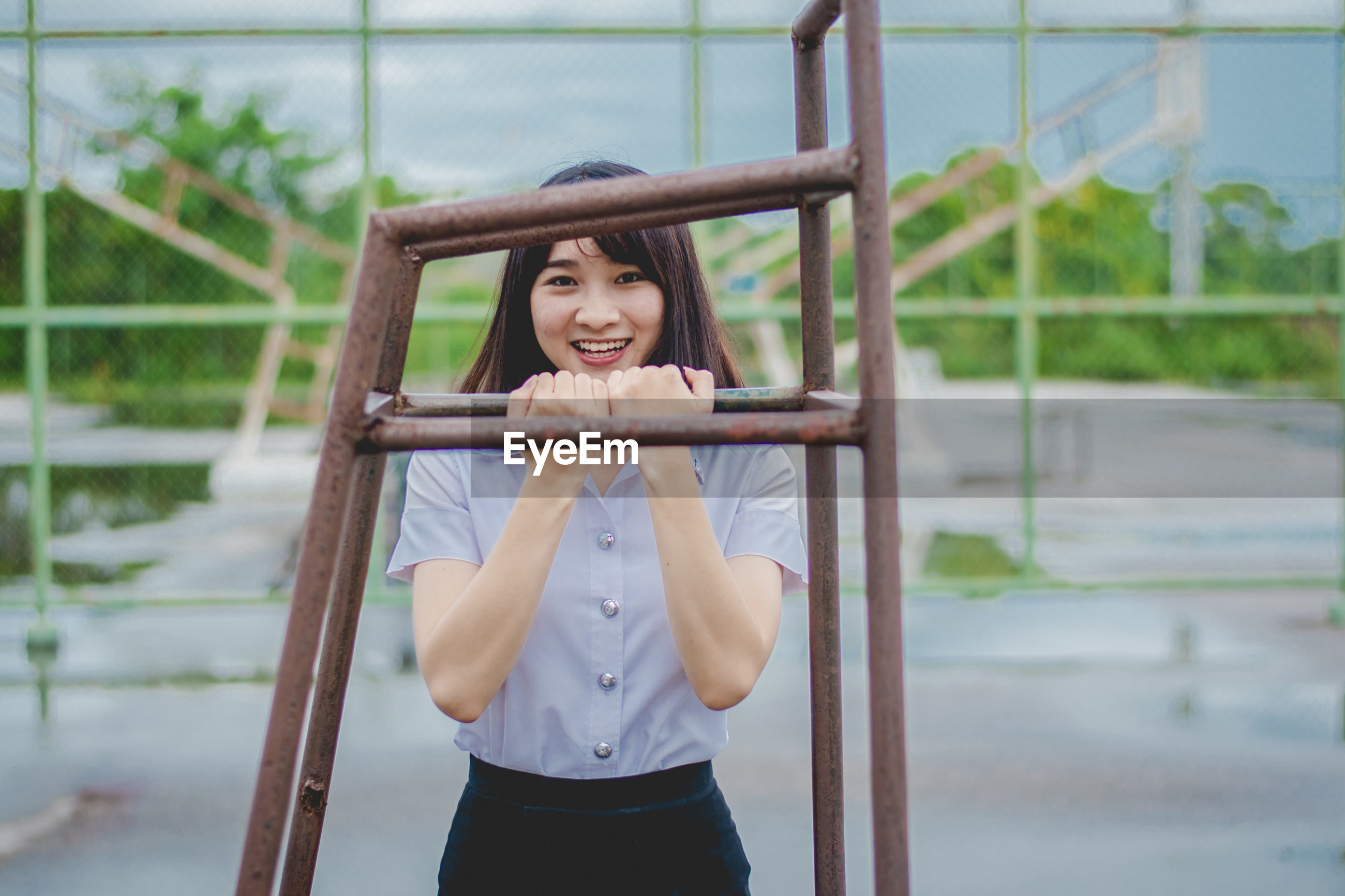 Portrait of smiling young woman standing by metal at playground during rainy season
