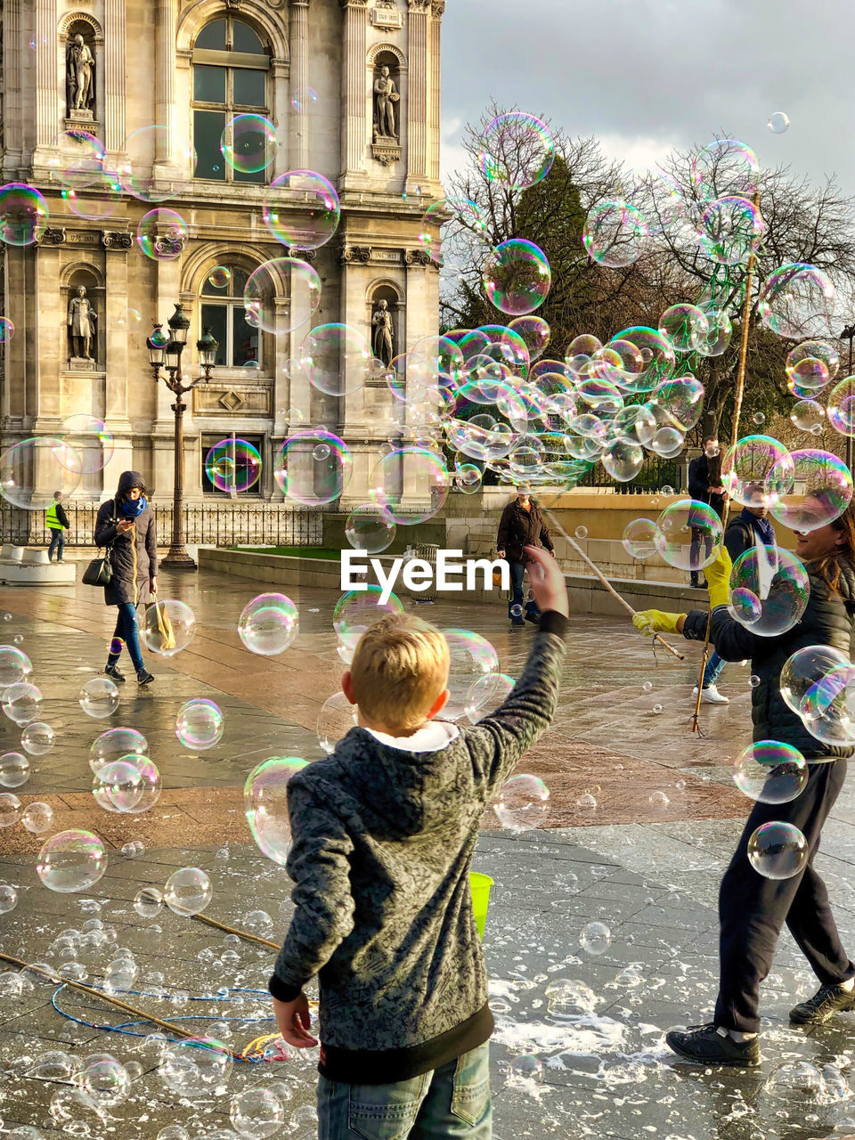 bubble, men, child, group of people, real people, boys, city, childhood, women, architecture, males, day, street, built structure, people, building exterior, females, standing, leisure activity, lifestyles, outdoors