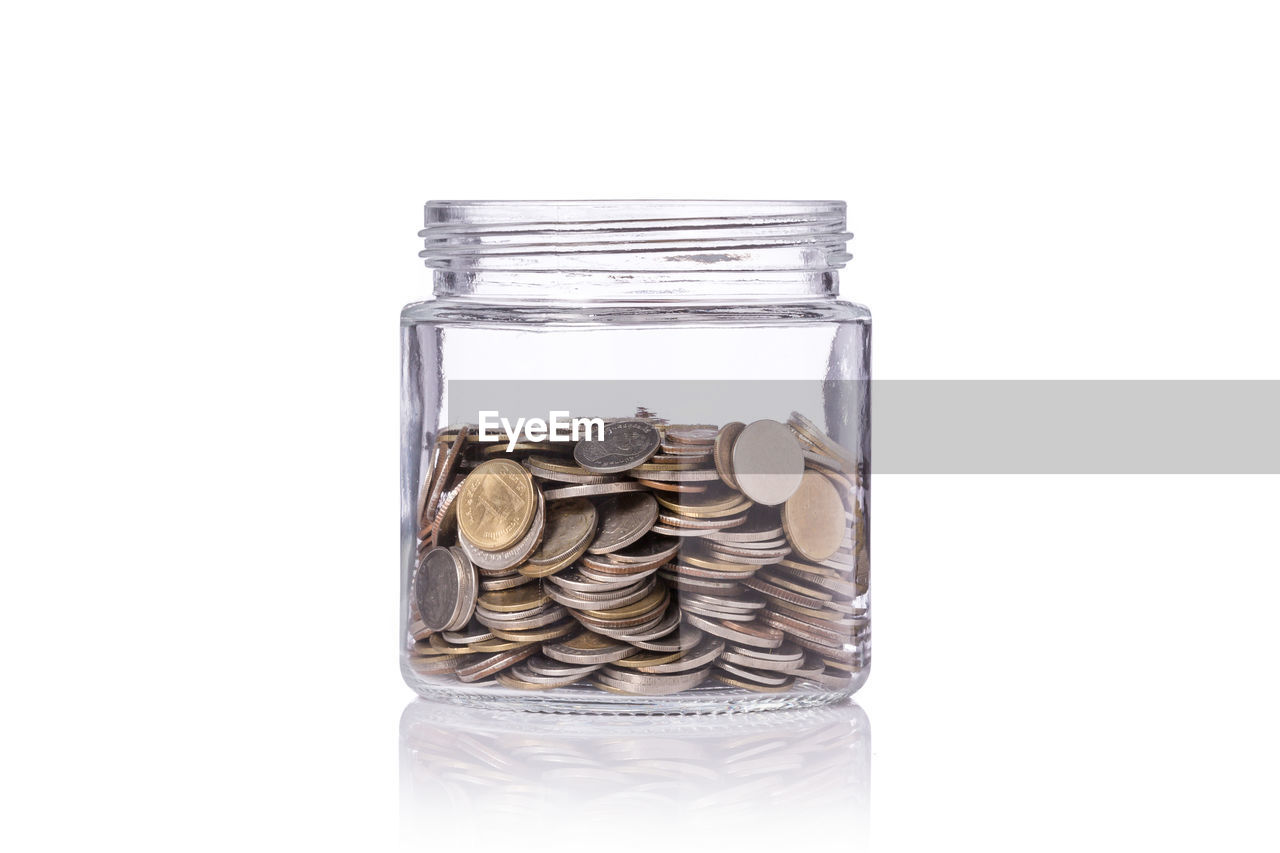 studio shot, large group of objects, container, coin, indoors, white background, close-up, savings, finance, currency, jar, still life, transparent, no people, wealth, business, abundance, stack, copy space, glass - material, economy