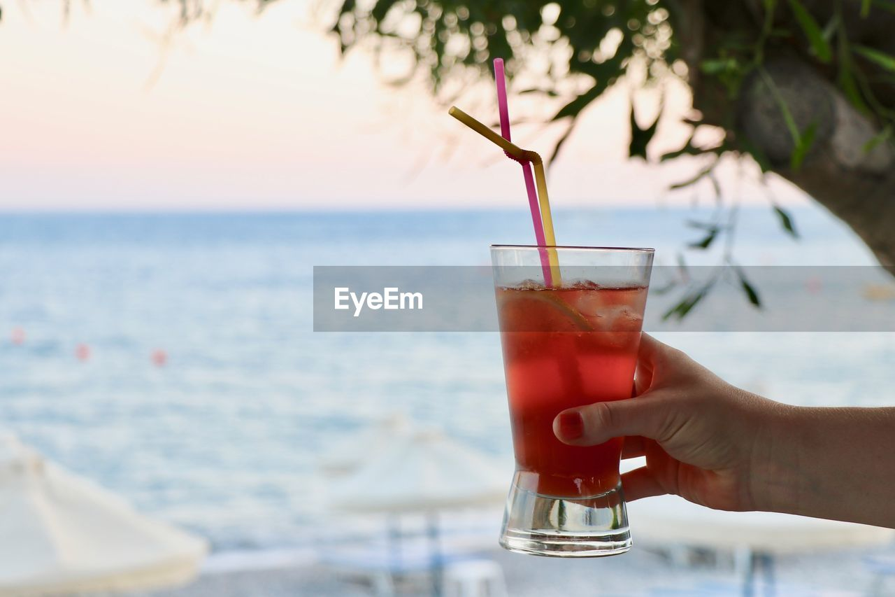 drink, refreshment, human hand, food and drink, water, hand, glass, household equipment, drinking glass, human body part, sea, alcohol, freshness, lifestyles, one person, sky, real people, nature, holding, horizon over water, cocktail, outdoors
