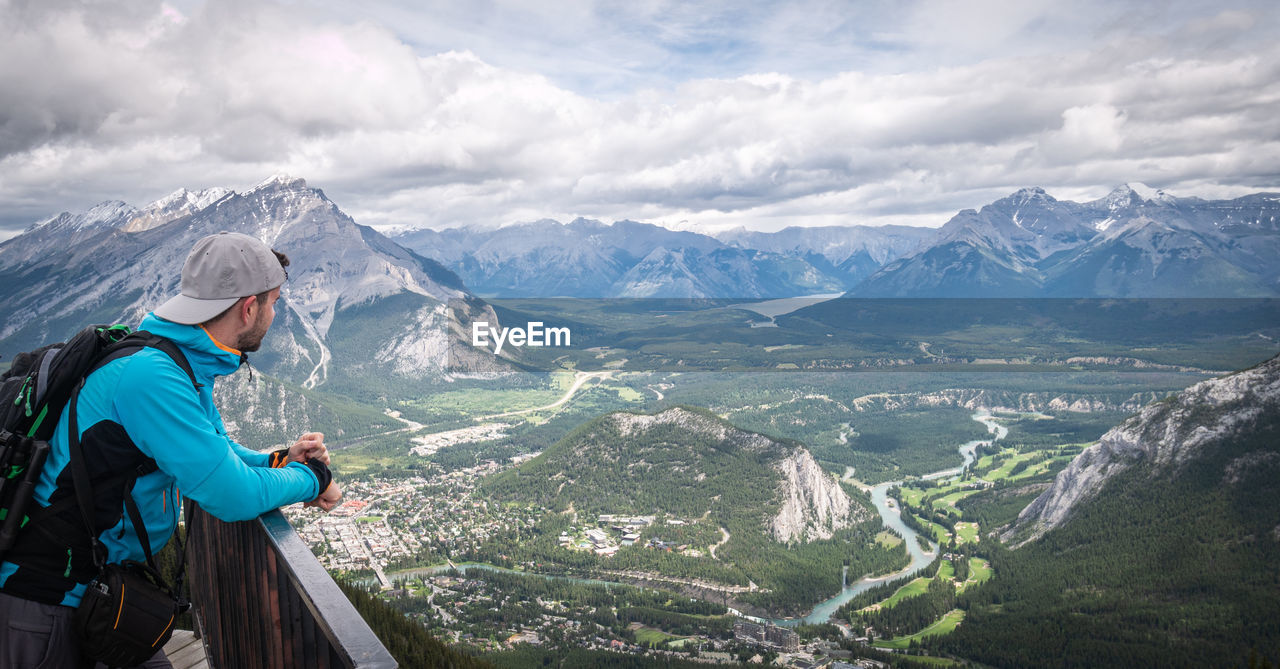 Side view of woman looking at mountains against sky