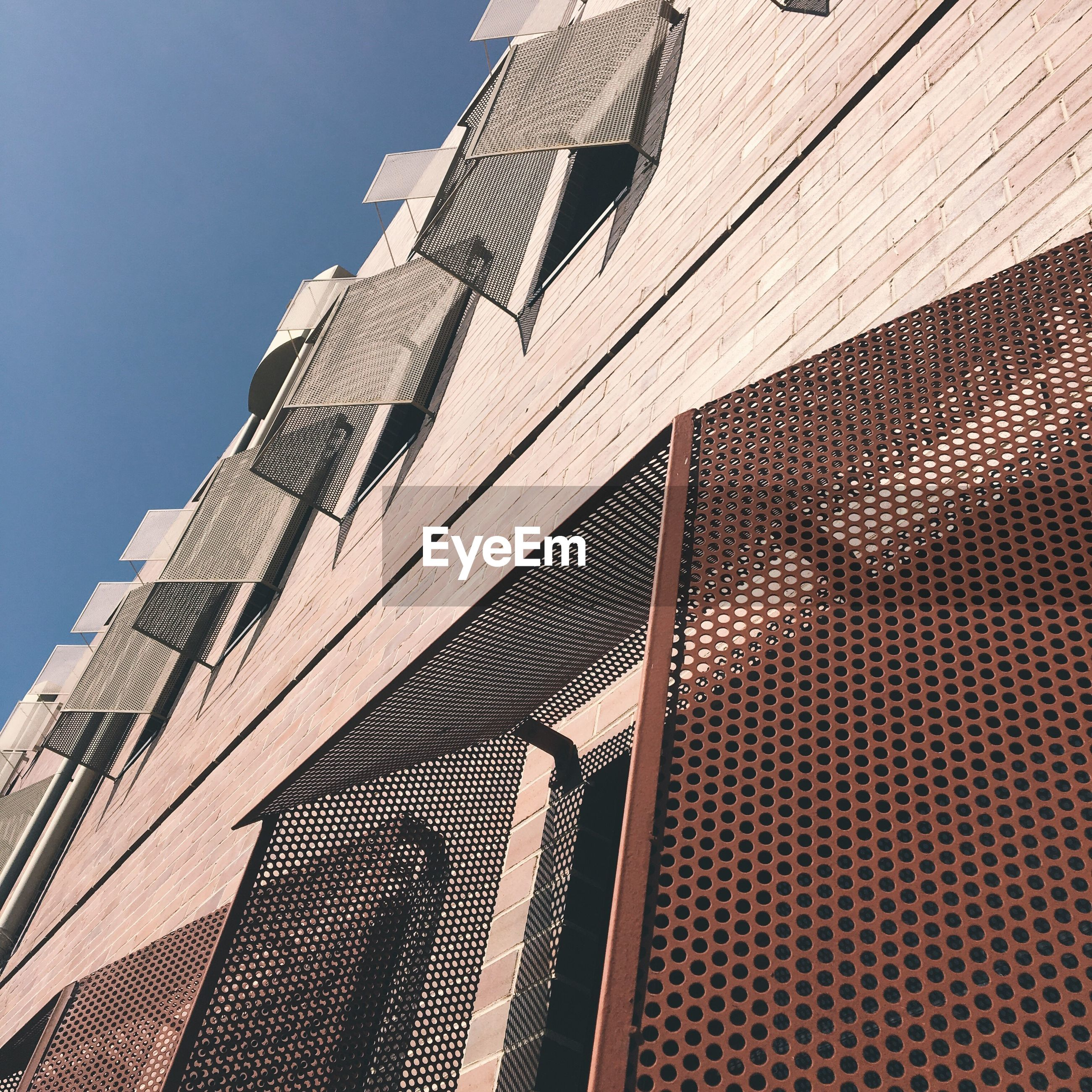 architecture, low angle view, built structure, building exterior, brick wall, tall - high, skyscraper, city, tower, day, blue, outdoors, architectural feature, tall, modern, sky, office building, no people, high section