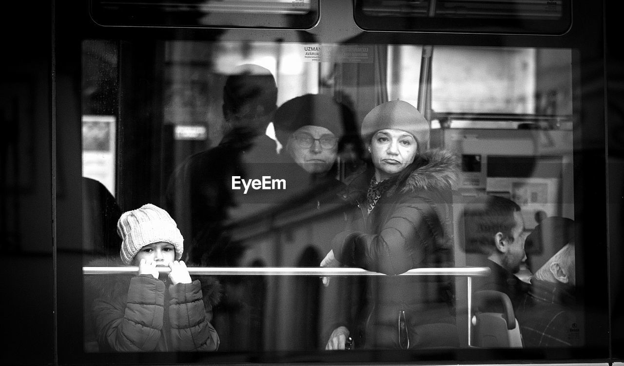 vehicle interior, real people, train - vehicle, public transportation, transportation, lifestyles, mode of transport, window, sitting, land vehicle, looking at camera, subway train, young women, indoors, childhood, portrait, young adult, day, one person, people