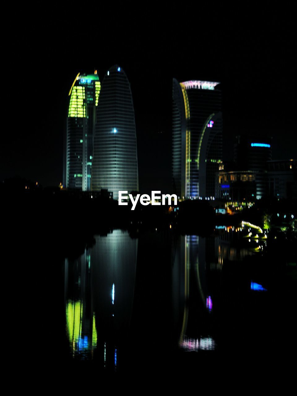 Low Angle View Of Illuminated City Buildings Reflected On Sea