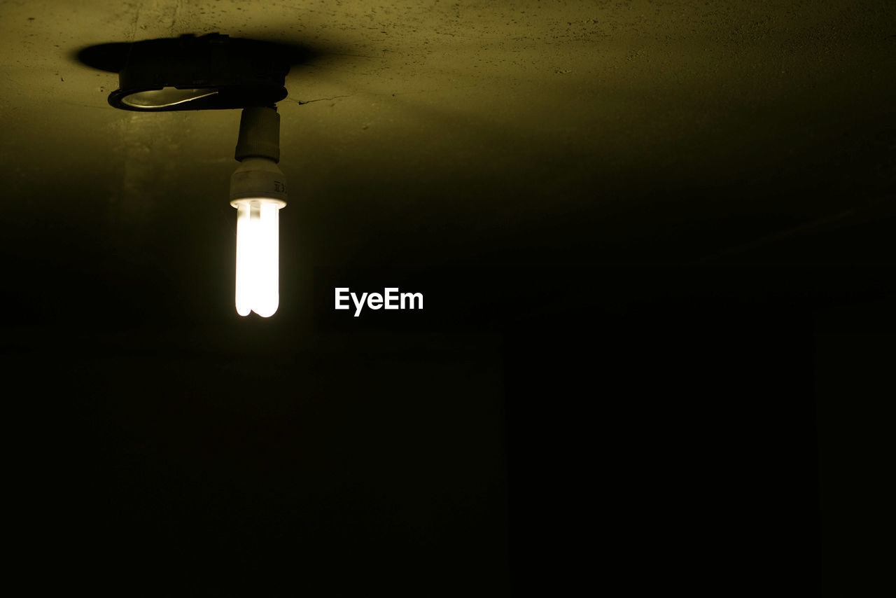 lighting equipment, electricity, illuminated, light, low angle view, light bulb, indoors, no people, dark, wall - building feature, glowing, electric light, darkroom, light - natural phenomenon, night, copy space, technology, electric lamp, ceiling, close-up, fluorescent light, light fixture, electrical equipment