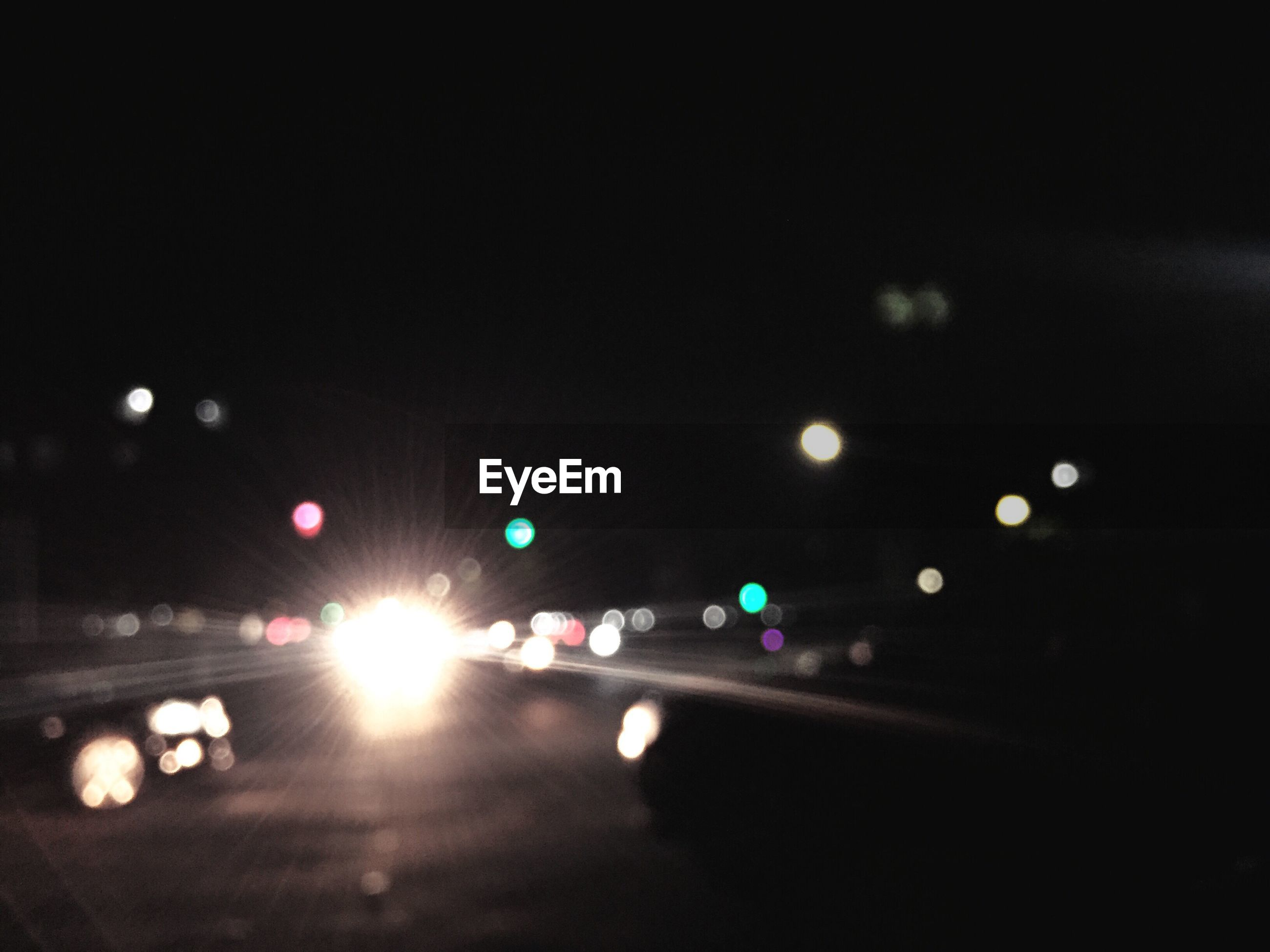 Defocused image of cars on road in city at night