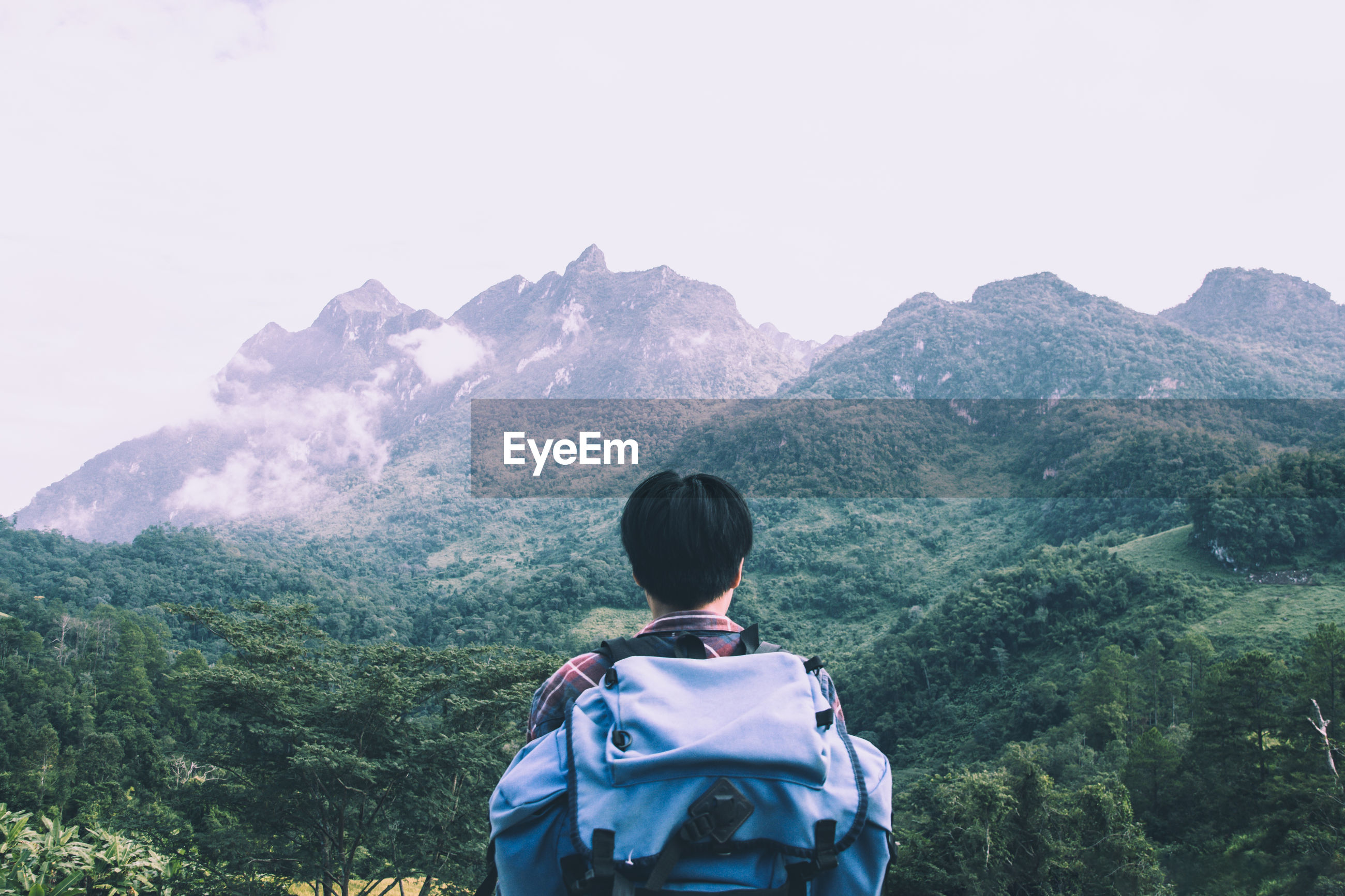 Rear view of backpacker looking at mountains while hiking in forest