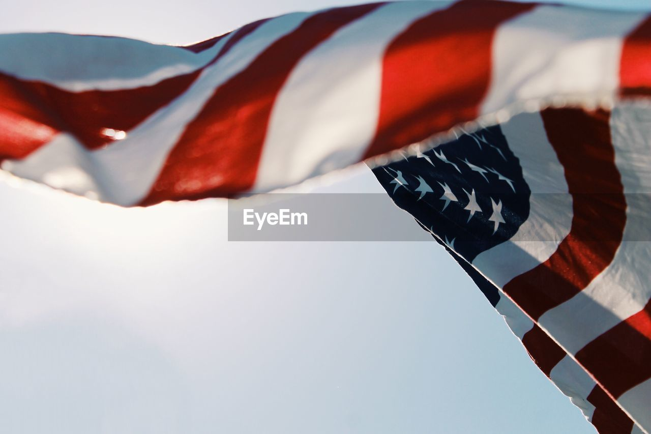 Low angle view of american flag against sky