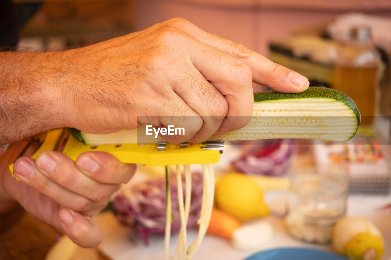 human hand, hand, human body part, one person, food, food and drink, real people, holding, indoors, lifestyles, freshness, body part, focus on foreground, finger, unrecognizable person, human finger, men, vegetable, selective focus