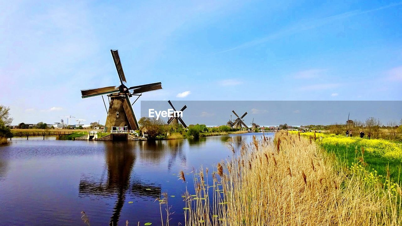 Reflection of traditional windmill by river against blue sky on sunny day