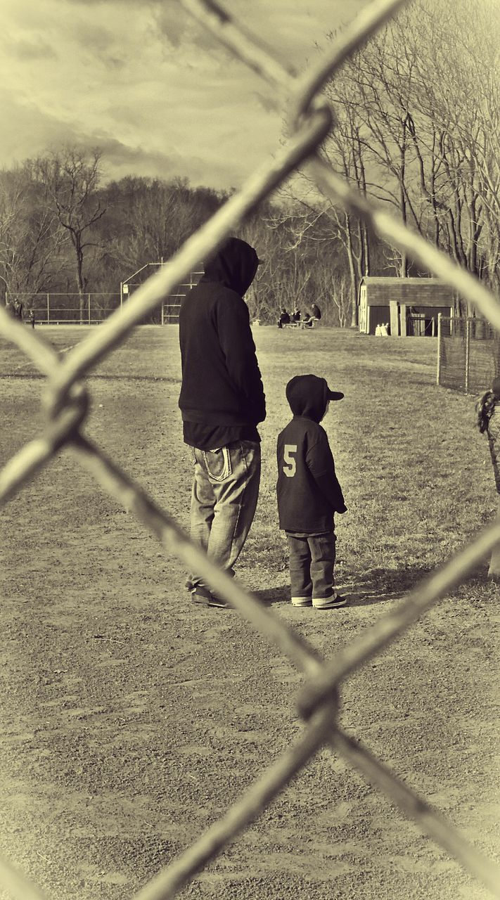 childhood, full length, real people, focus on background, chainlink fence, leisure activity, togetherness, two people, playing, boys, day, bonding, casual clothing, outdoors, field, lifestyles, elementary age, girls, standing, nature, child, people