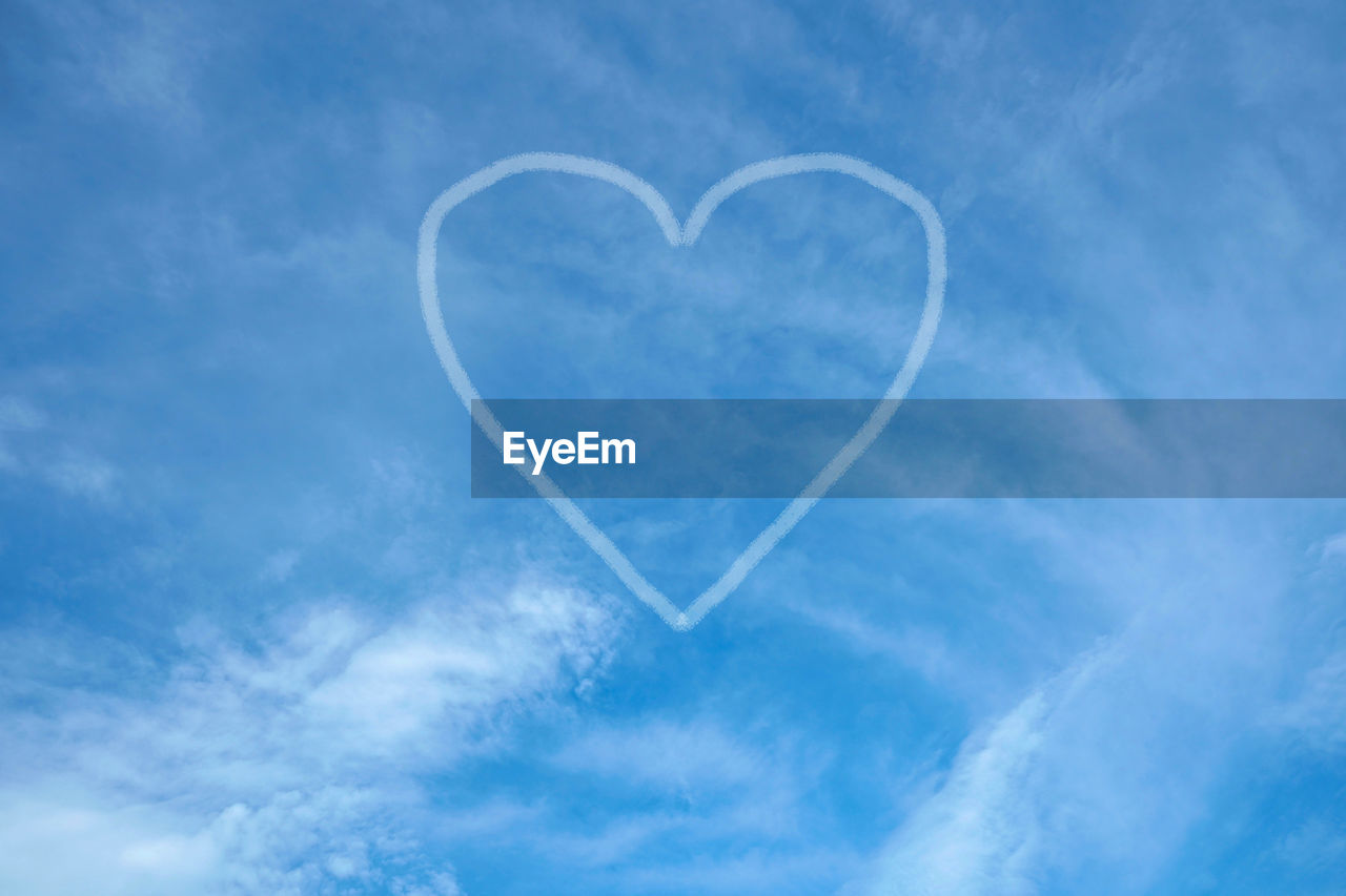 Low angle view of heart shape made from vapor trail in blue sky