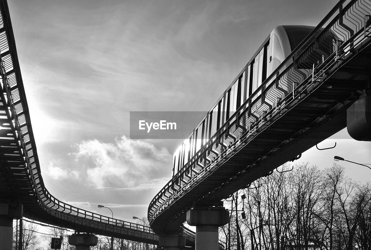 Low angle view of monorail on bridge against sky