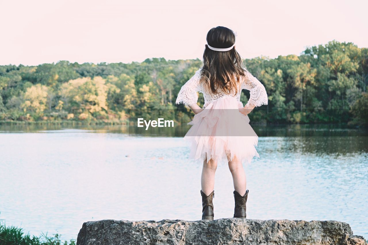 Rear View Of Girl Wearing Dress While Standing On Rock Against Lake