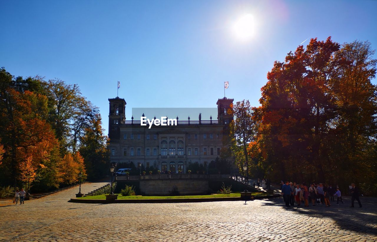architecture, sky, plant, tree, building exterior, built structure, nature, autumn, change, sunlight, clear sky, day, park, building, the past, history, city, travel destinations, incidental people, sun, outdoors
