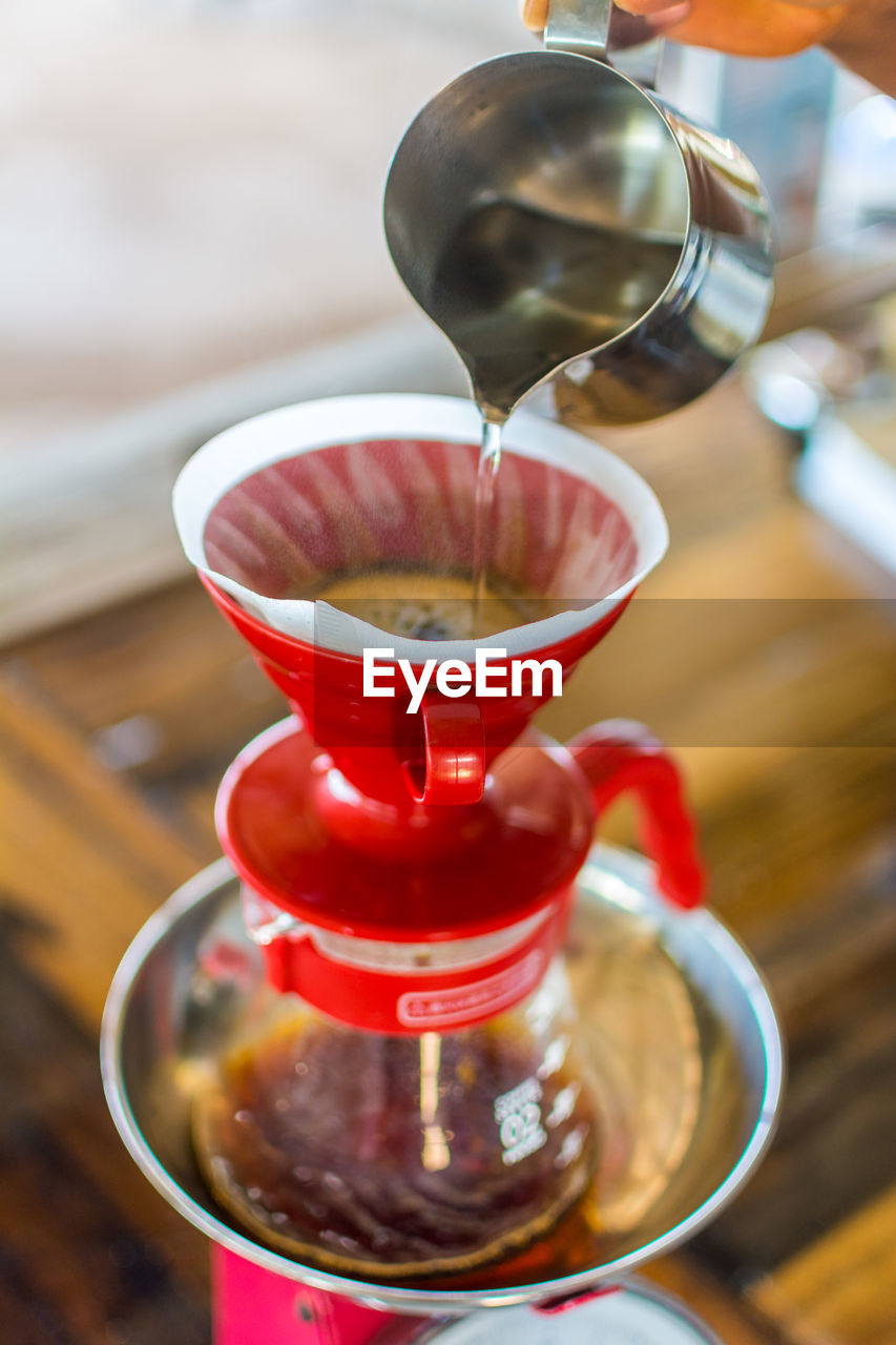 Cropped Hand Preparing Coffee On Table