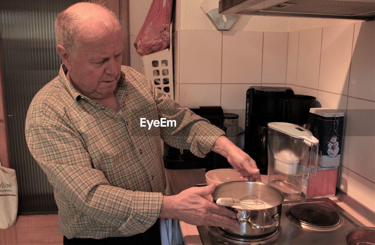 Man preparing food in kitchen at home