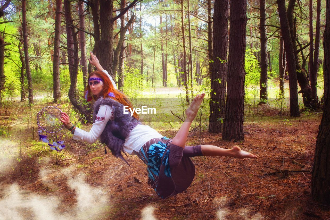 Full Length Portrait Of Woman With Dreamcatcher Levitating In Forest