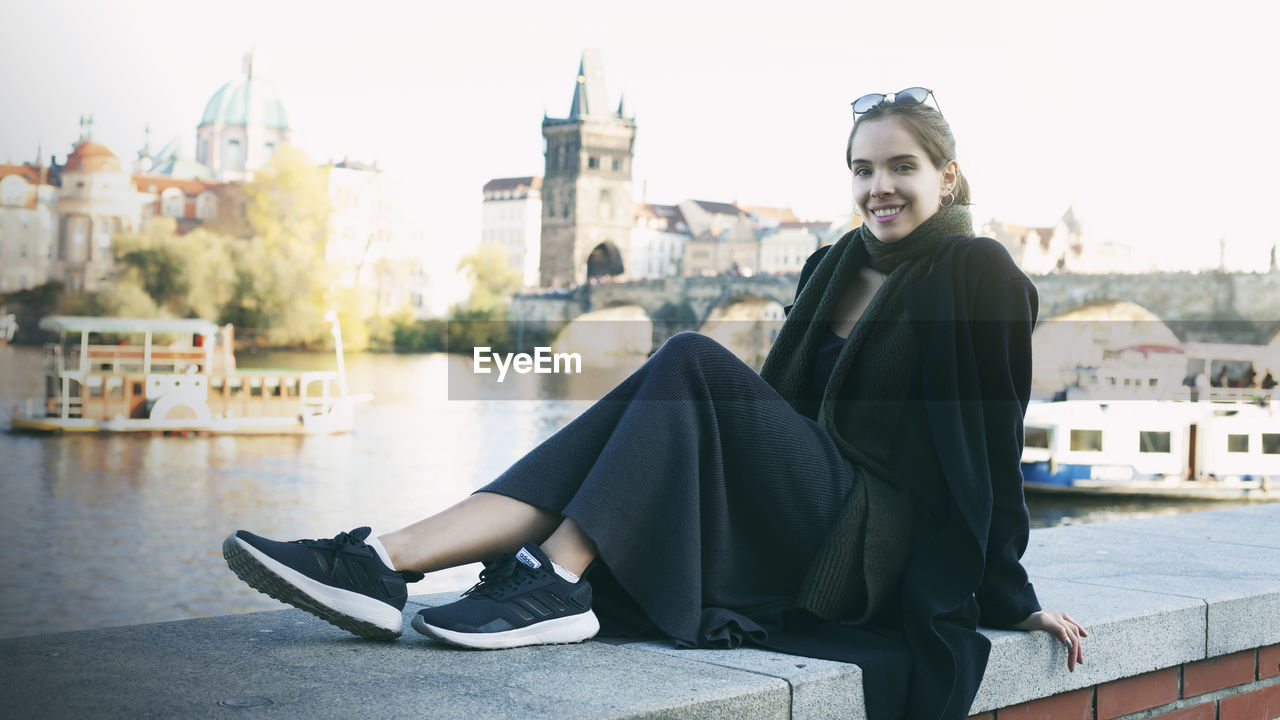 Portrait of beautiful young woman sitting in city