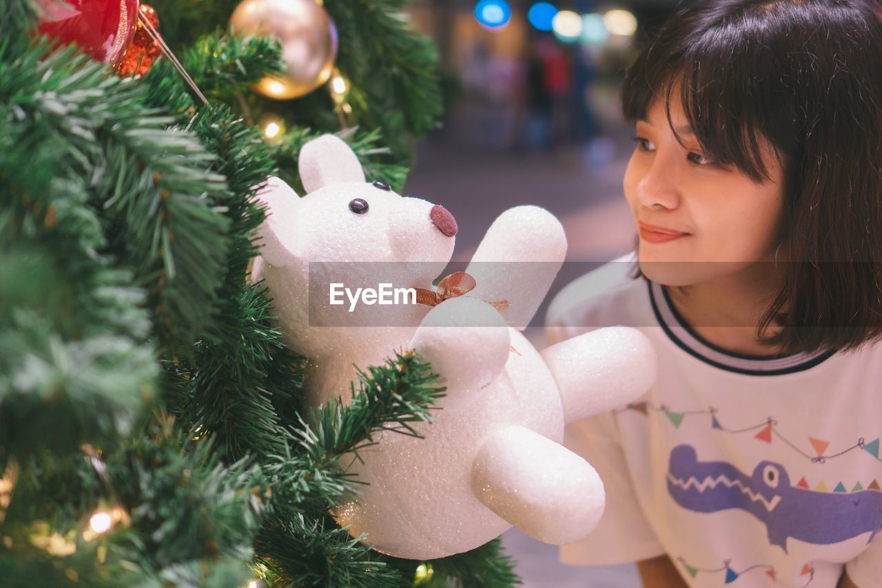 Young woman looking at stuffed toy hanging from christmas tree