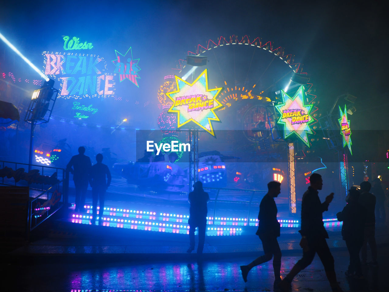 group of people, illuminated, night, men, real people, crowd, leisure activity, large group of people, silhouette, multi colored, motion, enjoyment, lifestyles, city, lighting equipment, arts culture and entertainment, women, adult, architecture, outdoors, light