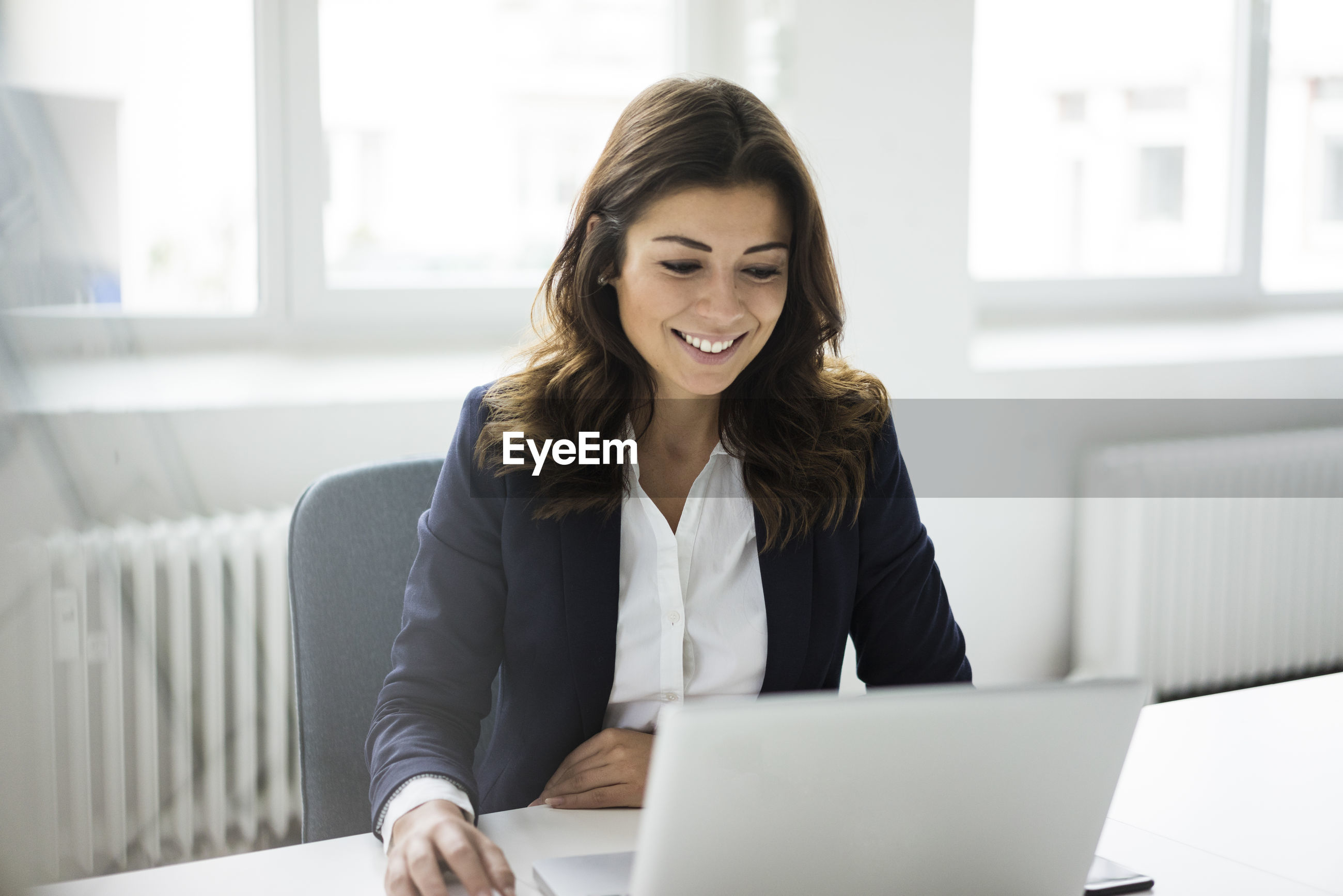 SMILING YOUNG WOMAN USING PHONE WHILE SITTING ON LAPTOP