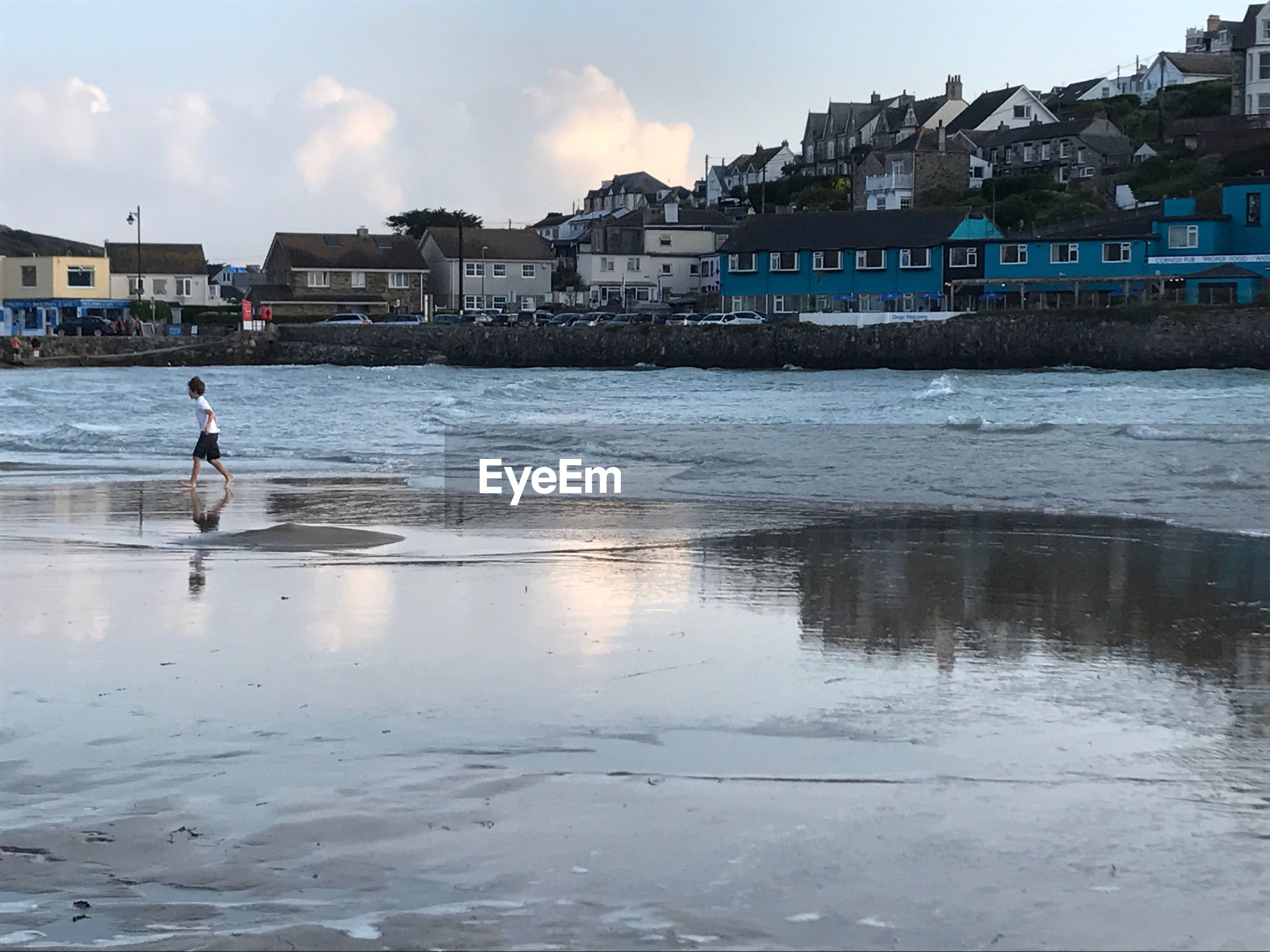 Boy running on shore at beach