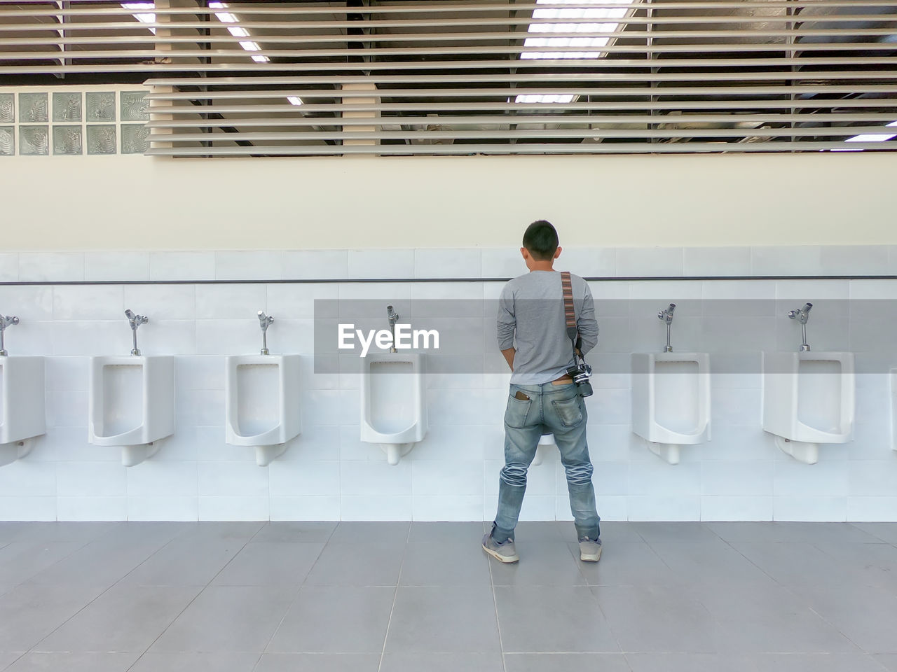 Rear View Of Man Standing At Public Urinal