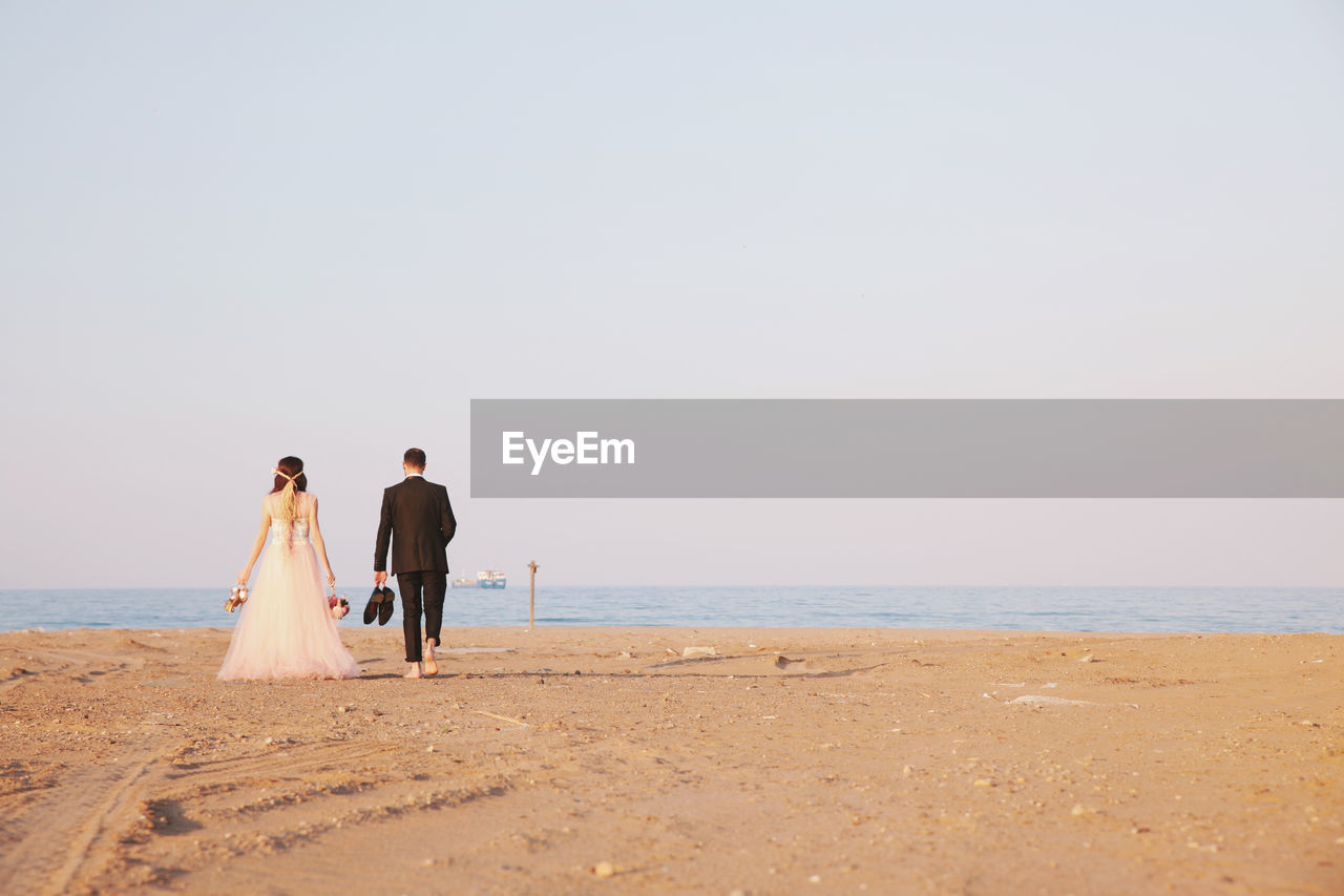 Rear View Of Bride And Groom On Beach