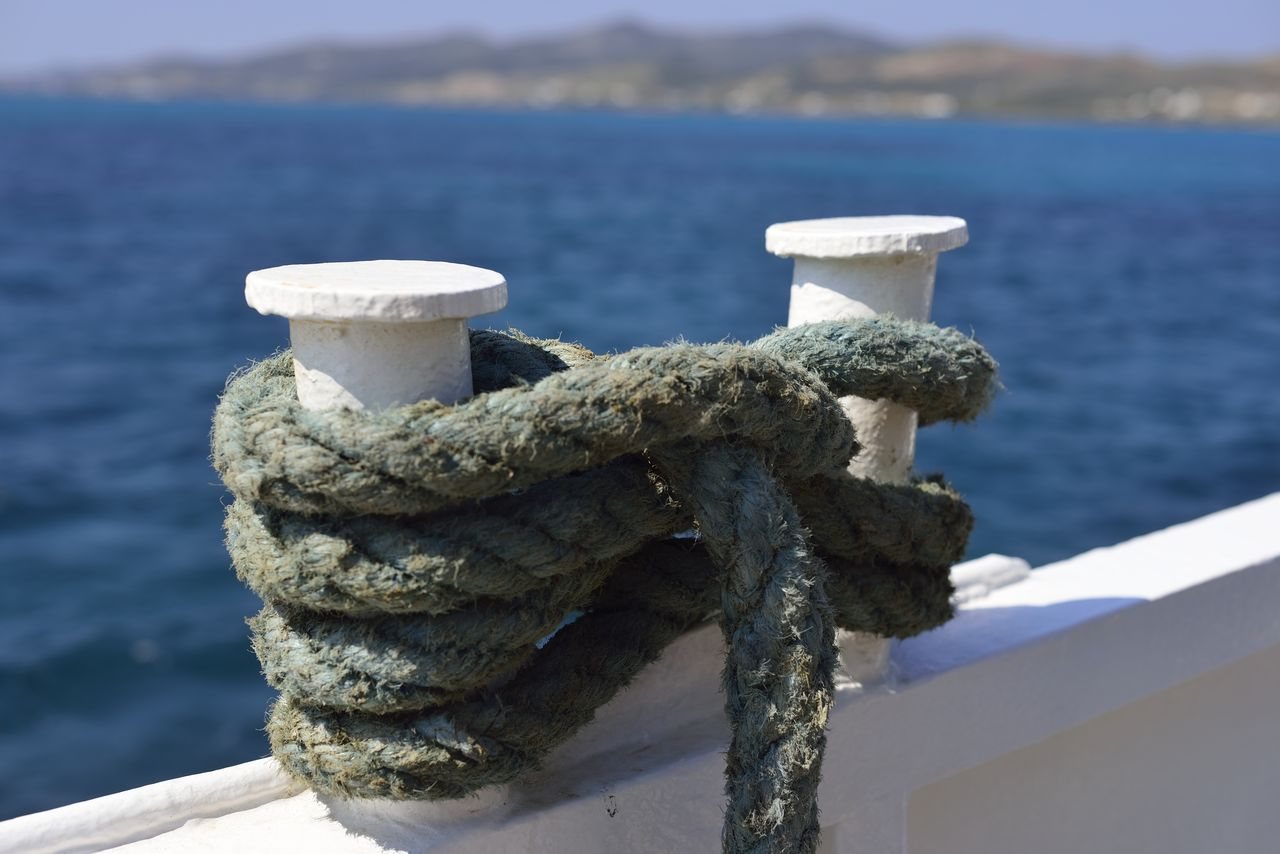 water, rope, focus on foreground, sea, day, no people, close-up, nature, bollard, post, outdoors, nautical vessel, sunlight, tied up, transportation, metal, strength, connection, mode of transportation