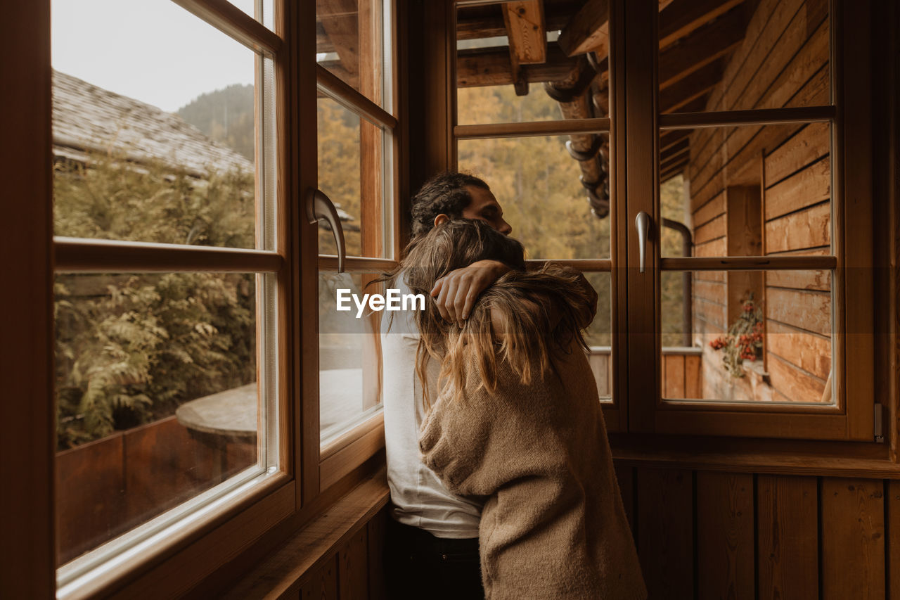 REAR VIEW OF WOMAN LOOKING AT WINDOW