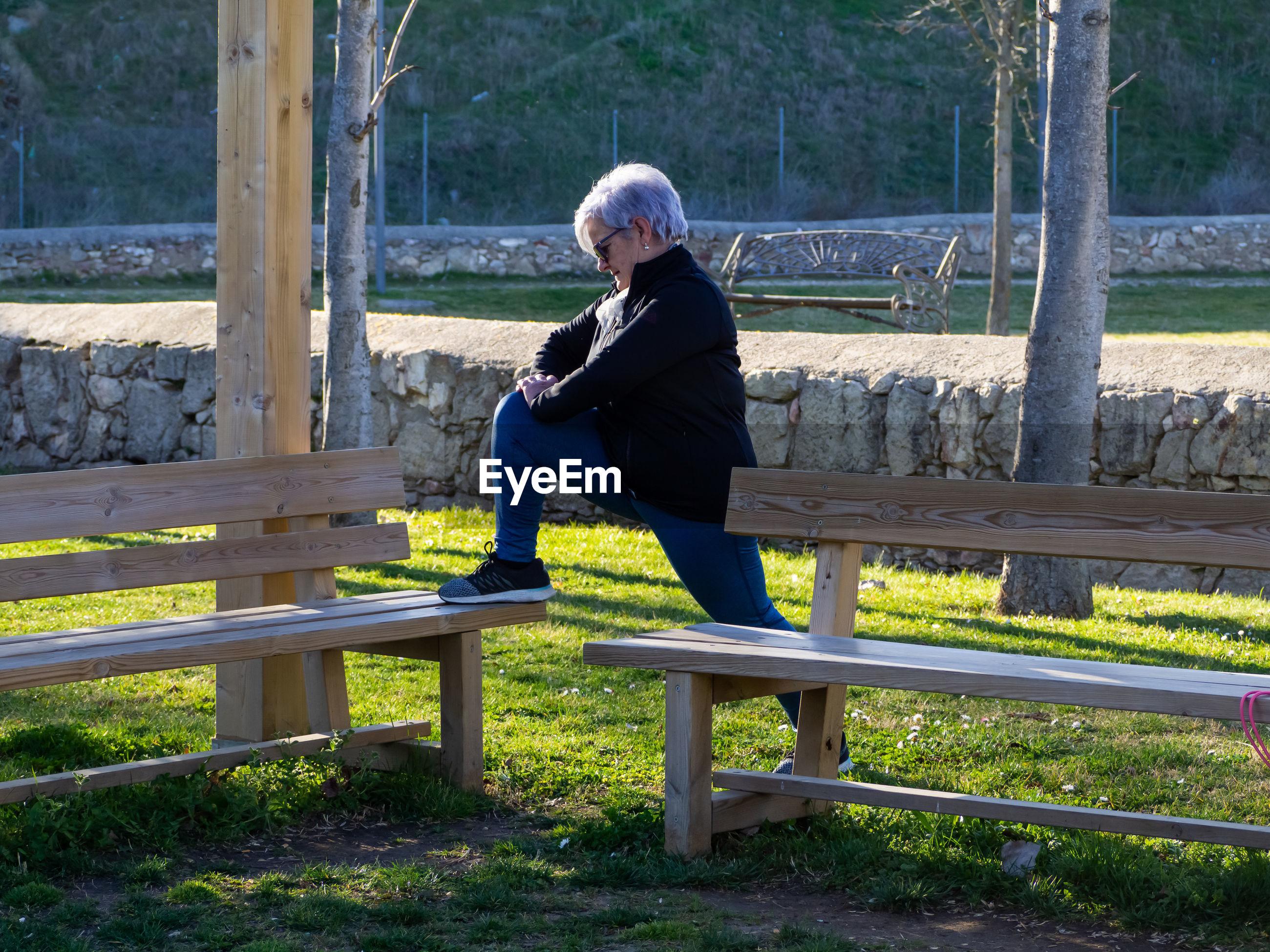 Full length of senior woman exercising in park
